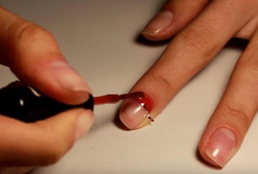 Закрасить красным лаком основание ногтя